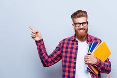 Uśmiechnięty młody nerdy czerwony brodaty elegancki uczeń stoi z obraz stock