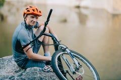 uśmiechnięty młody próbny rowerzysta relaksuje na skalistej falezie nad wodnym i przyglądającym zdjęcie stock