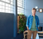 Uśmiechnięty młody przedsiębiorca stoi samotnie w nowożytnym biurze Obraz Stock