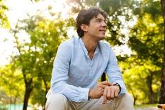 Uśmiechnięty młody przypadkowy mężczyzna przystosowywa jego mądrze zegarek fotografia stock