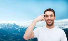 Uśmiechnięty młody przystojny mężczyzna wskazuje czoło zdjęcie royalty free
