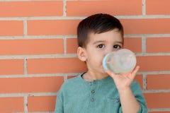 Uśmiechnięty małe dziecko bierze butelkę Obraz Royalty Free