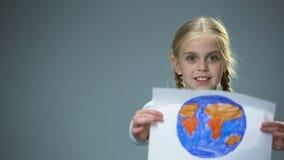 Uśmiechnięty małe dziecko seansu ziemi obrazek w kamerę, globalny pokoju pojęcie zbiory