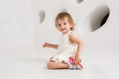Uśmiechnięty małej dziewczynki obsiadanie na podłoga na białym tle Fotografia Stock