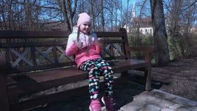 Uśmiechnięty mały dziewczyny łasowania lody i przedstawienie kciuk up zbiory wideo