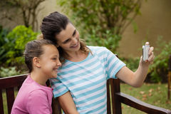 Uśmiechnięty macierzysty bierze selfie z córki obsiadaniem na ławce Fotografia Royalty Free
