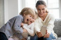 Uśmiechnięty macierzysty bierze selfie z dwa ślicznymi dzieciakami na smartphone zdjęcie stock