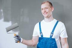 Uśmiechnięty malarz z farba rolownikiem obrazy stock