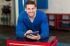Uśmiechnięty mechanik patrzeje kamerę używać pastylkę fotografia royalty free