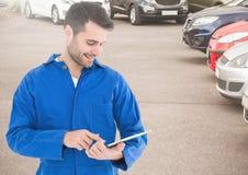 Uśmiechnięty mechanik używa cyfrową pastylkę w parking terenie Fotografia Royalty Free