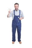 Uśmiechnięty mechanik z wyrwaniem lub spanner robi zwycięstwo gestowi Obraz Royalty Free