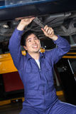 Uśmiechnięty mechanika naprawianie Pod Podnoszącym samochodem Obraz Royalty Free