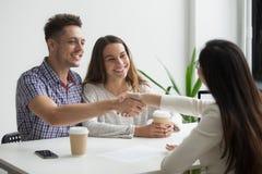 Uśmiechnięty millennial pary handshaking pośrednik handlu nieruchomościami lub advisor robić fotografia royalty free