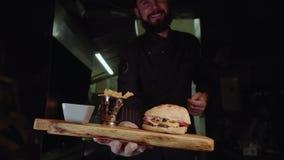 Uśmiechnięty mistrzowski szef kuchni w jednolitej patrzeje kamerze, trzyma półkowy z słuzyć hamburgerem zdjęcie wideo