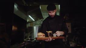 Uśmiechnięty mistrzowski szef kuchni w jednolitej patrzeje kamerze, trzyma półkowy z słuzyć hamburgerem zbiory wideo