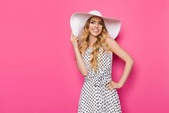 Uśmiechnięty moda model W Białym słońce kapeluszu Przeciw menchii ścianie Obrazy Royalty Free