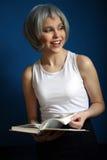 Uśmiechnięty model w srebnej peruce leafing przez książki z bliska niebieska tła Zdjęcia Stock