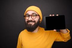 Uśmiechnięty modnisia mężczyzna pokazuje pastylkę Obraz Royalty Free
