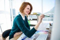uśmiechnięty modnisia projektant wnętrz patrzeje jej komputer Fotografia Royalty Free