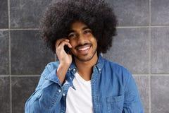 Uśmiechnięty murzyn używa telefon komórkowego Fotografia Royalty Free
