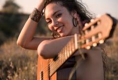 Uśmiechnięty Nagi Kędzierzawy brunetki dziewczyny obsiadanie z gitarą w polu obrazy royalty free