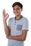 Uśmiechnięty nastoletni chłopak gestykuluje zadowalającego ręka znaka Fotografia Stock