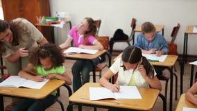 Uśmiechnięty nauczyciel pomaga brunetka ucznia zbiory