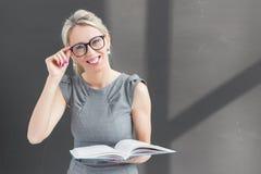 Uśmiechnięty nauczyciel stoi przed blackboard i trzyma książkę z szkłami Zdjęcia Royalty Free