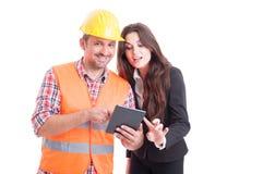 Uśmiechnięty nowożytny budowniczy i biznesowa kobieta używa bezprzewodową pastylkę Obrazy Royalty Free