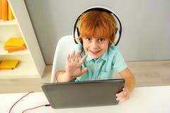 Uśmiechnięty nowożytny preschooler używa przenośnego komputer fotografia royalty free