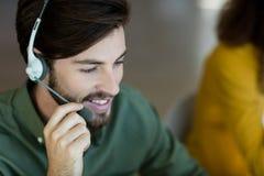 Uśmiechnięty obsługi klienta kierownictwo opowiada na słuchawki obrazy royalty free