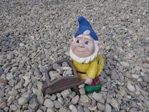 Uśmiechnięty ogródu karzeł z błękitnym kapeluszem, żółtą kurtką i wheelbarrow otoczaki, pełno zdjęcie royalty free