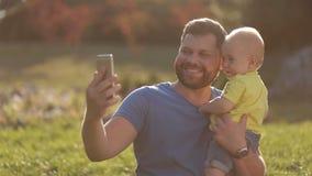 Uśmiechnięty ojca i dziecka syn robi selfie w parku zbiory wideo