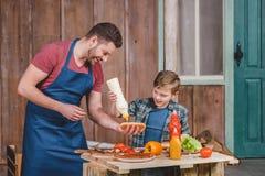 Uśmiechnięty ojca i syna narządzania hot dog w podwórku wpólnie Obrazy Stock
