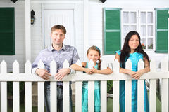 Uśmiechnięty ojca, macierzystego i małego córka stojak obok ogrodzenia, Obraz Stock