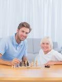 Uśmiechnięty ojciec bawić się szachy z jego synem Fotografia Stock