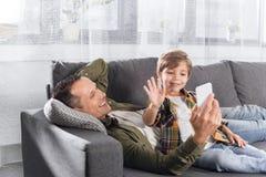 uśmiechnięty ojciec i mały syn używa smartphone podczas gdy odpoczywający na kanapie obrazy royalty free