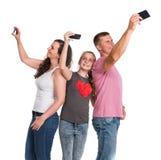 Uśmiechnięty ojciec, matka i córka bierze selfie smartphones, Zdjęcia Stock