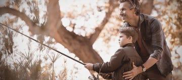 Uśmiechnięty ojciec pomaga syna podczas gdy łowiący w lesie fotografia stock