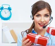 Uśmiechnięty operatora siedzenie przy stołem z czerwonym prezenta pudełkiem. Szczęśliwy biznes zdjęcia royalty free