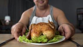 Uśmiechnięty otyły męski patrzeje grubas piec na grillu kurczaka, przejadać się i szybkiego żarcia, zdjęcie royalty free