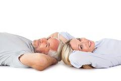 Uśmiechnięty pary lying on the beach i patrzeć kamerę Zdjęcie Royalty Free