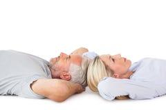 Uśmiechnięty pary lying on the beach i przyglądający up Zdjęcie Royalty Free