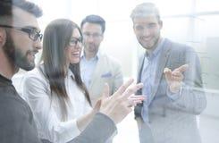 Uśmiechnięty personel dyskutuje coś stoi w biurze obraz royalty free
