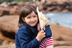 Uśmiechnięty piękny dzieciak słucha ocean z seashell dla wspominek Obrazy Stock