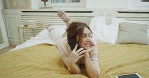 Uśmiechnięty piękny młodej damy mówienie na telefonie na jej sypialni, kłaść w dół w jej łóżku zdjęcie wideo