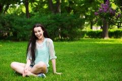 Uśmiechnięty piękny młodej kobiety obsiadanie na trawie Zdjęcia Royalty Free