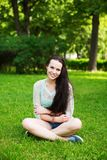 Uśmiechnięty piękny młodej kobiety obsiadanie na trawie Obraz Royalty Free
