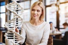 Uśmiechnięty piękny młody studencki studiuje DNA model Zdjęcia Stock