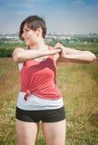 Uśmiechnięty piękny plus wielkościowa kobieta w sportswear robi ćwiczeniu Obrazy Stock